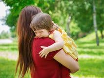 拿着有泪花的母亲哭泣的女婴 免版税库存图片
