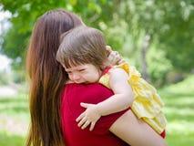 拿着有泪花的母亲哭泣的女婴 库存照片
