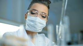 拿着有液体样品的年轻女性科学家试管做研究对临床实验室 股票视频