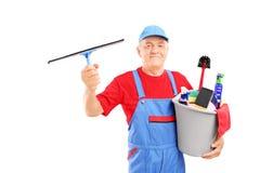 拿着有清洁物品和看的男性擦净剂一个桶 图库摄影