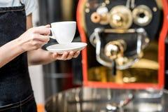 拿着有烘烤器机器的一个咖啡杯在背景 免版税库存照片