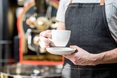 拿着有烘烤器机器的一个咖啡杯在背景 免版税库存图片