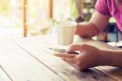 拿着有热的咖啡杯的美好的年轻行家妇女` s手流动巧妙的电话在咖啡馆购物 库存照片