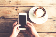 拿着有热的咖啡杯的美好的年轻行家妇女` s手流动巧妙的电话在咖啡馆购物 免版税图库摄影