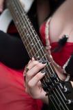 拿着有焦点的性感的红色礼服的妇女电吉他在她的在吉他脖子串的手上 库存图片