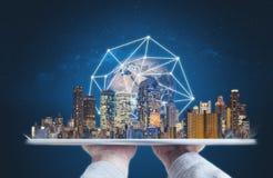 拿着有现代大厦全球网络连接技术全息图的手数字片剂 这个图象的元素是furnis 免版税图库摄影
