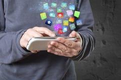 拿着有现代五颜六色的浮动apps和象的妇女一个智能手机 免版税图库摄影