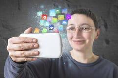 拿着有现代五颜六色的浮动apps和象的妇女一个智能手机 免版税库存图片