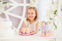 拿着有甜点的小女孩一块桃红色板材在棒棒糖结块 图库摄影