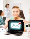 拿着有电子邮件标志的女孩膝上型计算机在学校 免版税库存图片