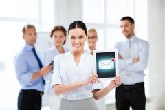 拿着有电子邮件标志的女实业家片剂个人计算机 免版税库存照片
