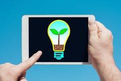 拿着有电灯泡eco概念例证的人一个片剂设备 免版税库存图片