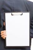 拿着有白皮书的手剪贴板 库存图片