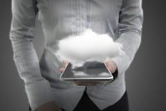 拿着有白色云彩的妇女手巧妙的电话 免版税库存图片