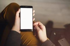 拿着有白色屏幕的Pov视图年轻女性手智能手机,当坐户内时 库存照片