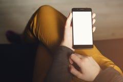 拿着有白色屏幕的Pov视图年轻女性手智能手机,当坐户内时 免版税图库摄影