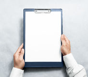 拿着有白色a4纸设计大模型的手空白的剪贴板 库存照片