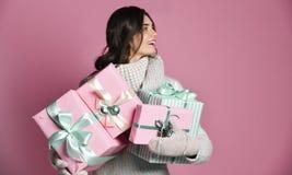 拿着有礼物的快乐的妇女很多箱子在桃红色背景 免版税图库摄影