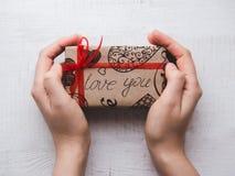 拿着有礼物的手一个箱子,栓由丝带 免版税库存照片