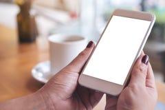 拿着有空白的桌面屏幕和咖啡杯的妇女` s手白色手机在咖啡馆 免版税库存图片