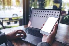 拿着有空白的白色屏幕的女商人的大模型图象手机,当使用膝上型计算机时 库存照片