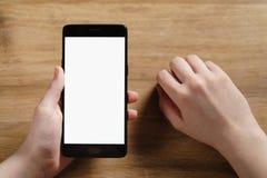 拿着有空白的白色屏幕的女性青少年的手智能手机 图库摄影