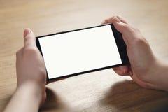 拿着有空白的白色屏幕的女性青少年的手智能手机 库存图片