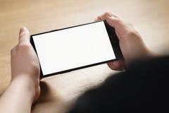 拿着有空白的白色屏幕的女性青少年的手智能手机 免版税库存照片