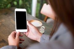 拿着有空白的白色屏幕的手白色手机有在木桌上的热的咖啡杯的在咖啡馆 免版税库存照片