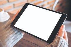 拿着有空白的白色屏幕的手黑片剂个人计算机有在木桌上的加奶咖啡杯子的在咖啡馆 免版税库存照片