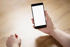 拿着有空白的白色屏幕的年轻人手智能手机 库存照片