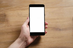 拿着有空白的白色屏幕的年轻人手智能手机 免版税图库摄影