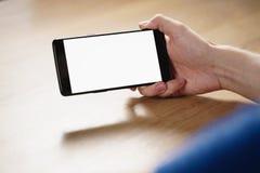 拿着有空白的白色屏幕的年轻人手智能手机 免版税库存图片