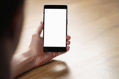 拿着有空白的白色屏幕的年轻人手智能手机 免版税库存照片