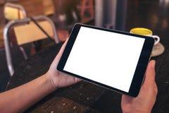 拿着有空白的白色桌面屏幕和咖啡杯的手黑片剂个人计算机在咖啡馆的木桌上 库存图片