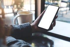 拿着有空白的白色桌面屏幕的妇女` s手黑手机有咖啡杯和膝上型计算机的在桌上在咖啡馆 免版税图库摄影