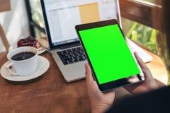 拿着有空白的绿色屏幕、膝上型计算机、咖啡杯和蛋糕的手的大模型图象黑片剂个人计算机在木桌上 免版税库存图片