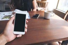 拿着有空白的黑屏幕、加奶咖啡杯子和妇女阅读书的人` s手的大模型图象白色手机 库存图片