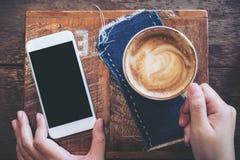 拿着有空白的黑屏幕和咖啡杯的手的大模型图象手机 库存照片