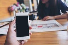 拿着有空白的黑屏幕的人` s手的大模型图象白色手机在现代咖啡馆和迷离妇女读书报纸 库存图片