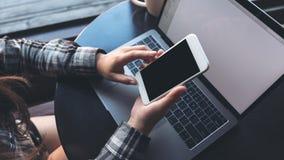 拿着有空白的黑屏幕的女商人的大模型图象手机,当使用在桌上时的膝上型计算机 免版税库存照片