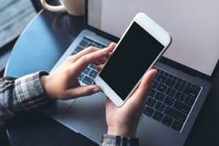 拿着有空白的黑屏幕的女商人的大模型图象白色手机有在木桌上的膝上型计算机的 免版税库存照片