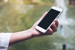 拿着有空白的黑桌面屏幕的妇女` s手白色巧妙的电话有迷离绿色自然背景 免版税图库摄影