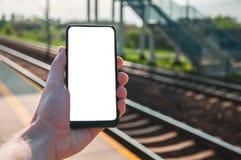 拿着有空白的,白色屏幕的手大模型一个智能手机,有火车站的在背景中 库存照片