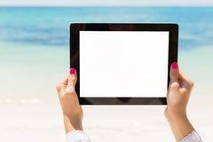 拿着有空的屏幕的妇女片剂计算机在海滩 免版税图库摄影