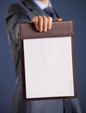 拿着有空的纸片的商人一张剪贴板 图库摄影