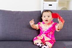 拿着有繁体中文衣物的亚裔婴孩红色口袋 图库摄影
