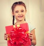 拿着有红色丝带弓的美丽的逗人喜爱的孩子女孩当前箱子 免版税库存图片