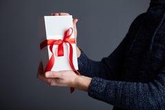拿着有红色丝带的一个人白色礼物盒在他的手上 免版税库存照片
