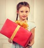 拿着有红色丝带的美丽的逗人喜爱的孩子女孩大当前箱子 免版税库存图片